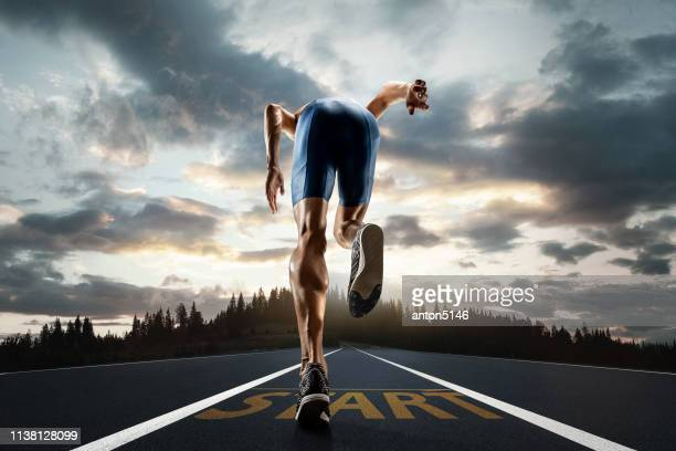 the close up feet of man running and training on running track - sprinting stock pictures, royalty-free photos & images