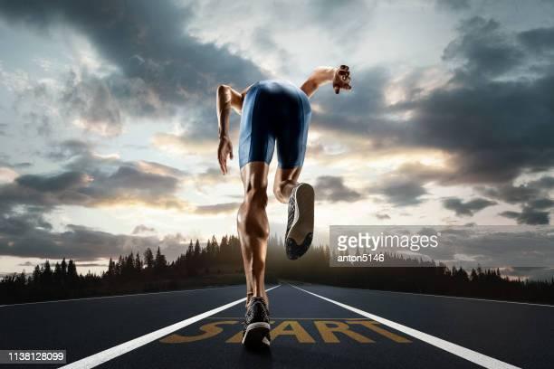 走っているトラックの上の男のランニングとトレーニングのクローズアップフィート - 短距離走 ストックフォトと画像