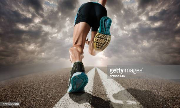 the close up feet of man running and training on running track - endurance stock photos and pictures