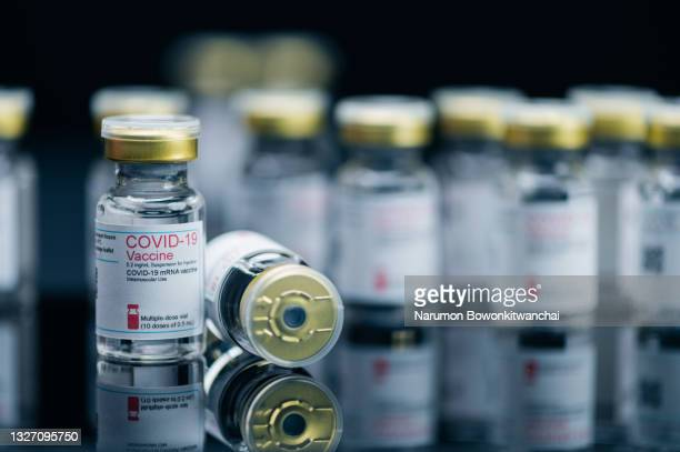 the close-up image of the covid-19 bottle with the black backdrop - generic drug stock pictures, royalty-free photos & images