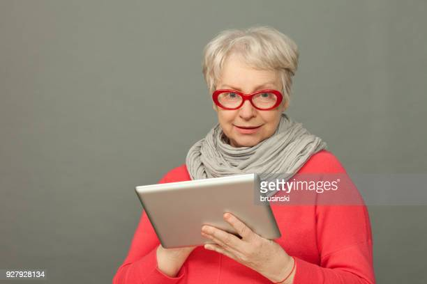the closeup studio portrait of the attractive senior 65-years-old woman using the tablet - 65 69 years stock pictures, royalty-free photos & images