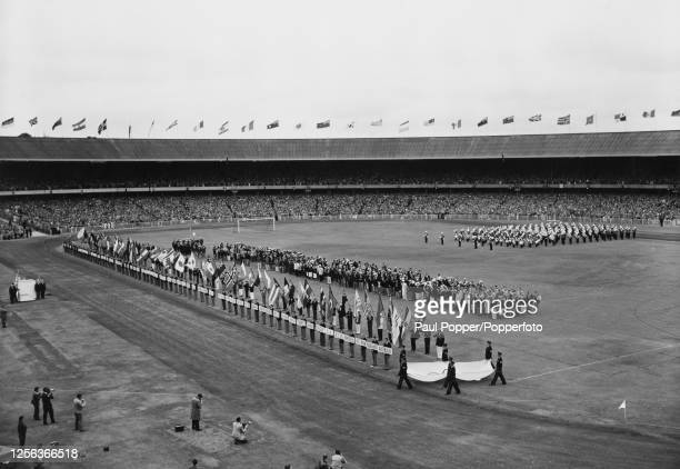 The closing ceremony of the 1956 Summer Olympics showing the Olympic flag being carried to the rostrum where it will be handed to Lord Mayor of...