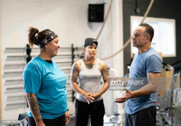 The coach, 55-years-old Senior Latino ma, talking with young athletic Hispanic women in the gym