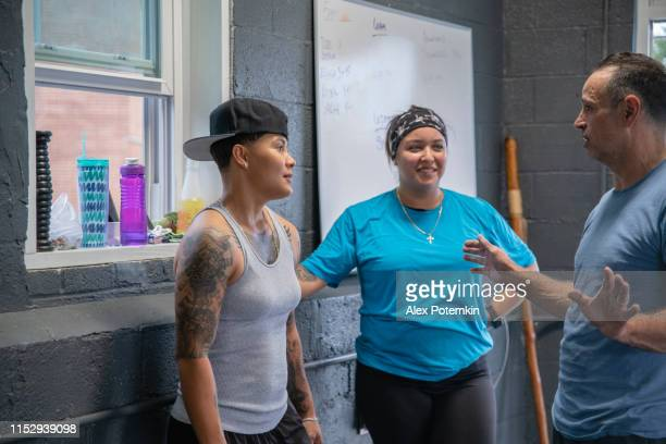 the coach, 55-years-old senior latino ma, talking with young athletic hispanic women in the gym - 55 59 years stock pictures, royalty-free photos & images