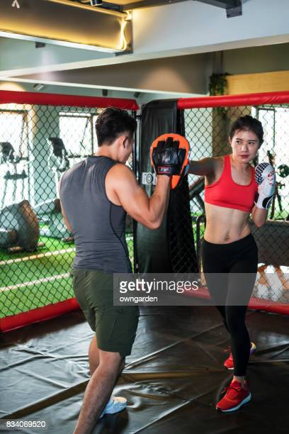 The coach coaching the fitness women in boxing