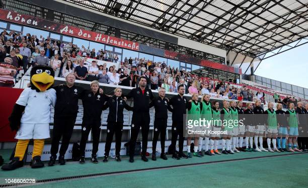 The coach he's and the team behind of Germany stands for the national anthem during the International friendly match between Germany Women and...