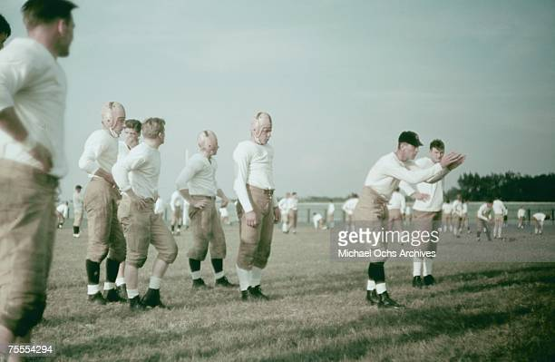 The coach instructs his players during a high school football practice circa 1939.