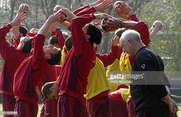 The coach of the Belgian national football team Aime Anthuenis stands next to his players as they warm up on the third day of training 23 March 2005...