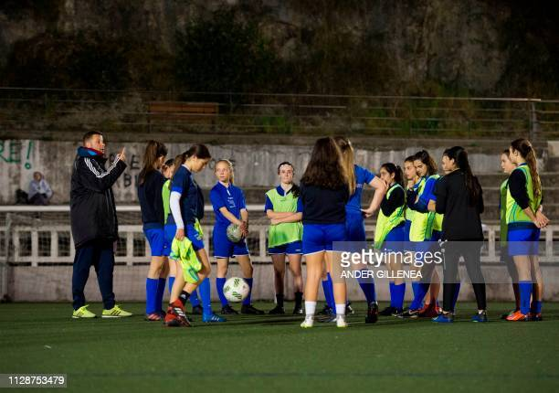 The coach speaks to Anorga KKE football school's girls during a training session in the Spanish Basque city of San Sebastian on February 18 2019