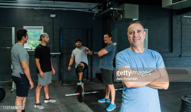 the coach, the senior latino hispanic man, posing in the front of the group of athletes in the gym - alex potemkin or krakozawr latino fitness stock photos and pictures