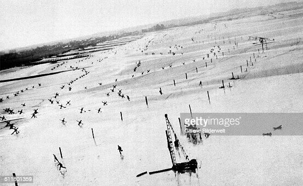 The coast in Normandy with German defense installations in front of the beach. 1944. A reconnaissance plane is flying over the defenses built to...