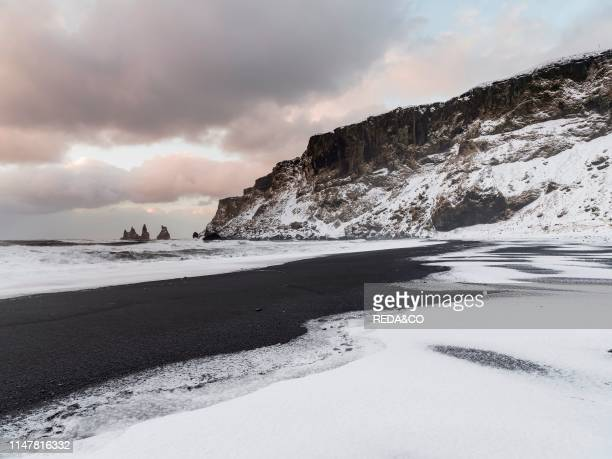 The coast of the north atlantic near Vik y Myrdal during winter Black volcanic beach with the sea stacks Reynisdrangar Europe Northern Europe...