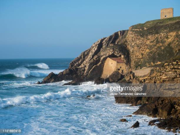 The coastal landscape of Cantabria, with the hermitage of Santa Justa at the base of the cliff, in Suances. Cantabrian sea.