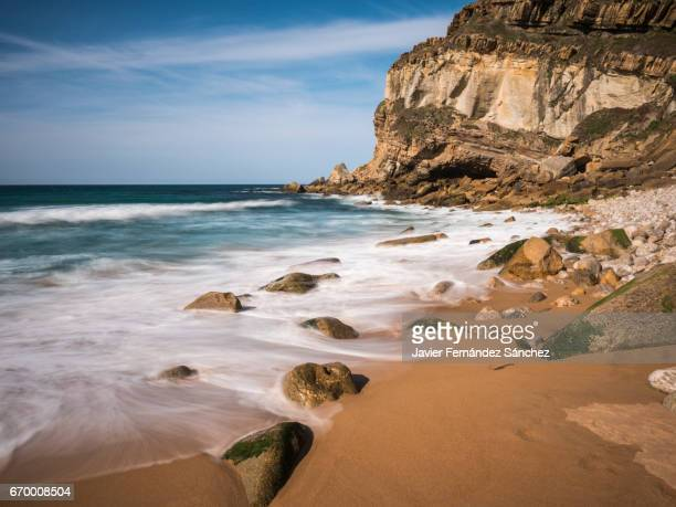 The coastal landscape of the Suances area with the foam of the Cantabric Sea waves covering the small wild beach of La Tablía. Cantabría, Spain.