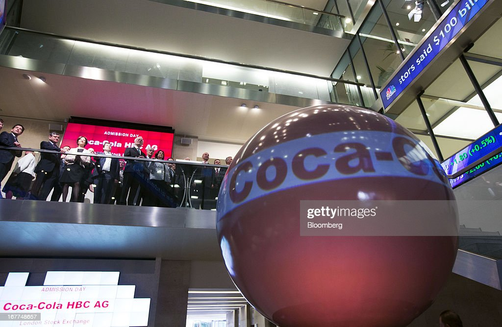 The Coca-Cola HBC (Hellenic Bottling Company) AG logo is displayed on a giant screen during the launch of the company's listing at the London Stock Exchange in London, U.K., on Monday, April 29, 2013. Coca-Cola HBC is shifting its primary listing to London from the Greek stock exchange in an effort to reduce exposure to Europe's sovereign-debt crisis and improve access to international investors. Photographer: Jason Alden/Bloomberg via Getty Images