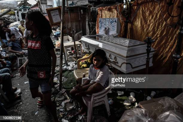 The coffin carrying the remains of Kenneth Trasmano who was killed in a police drug sting operation is seen next to strewn garbage during his funeral...