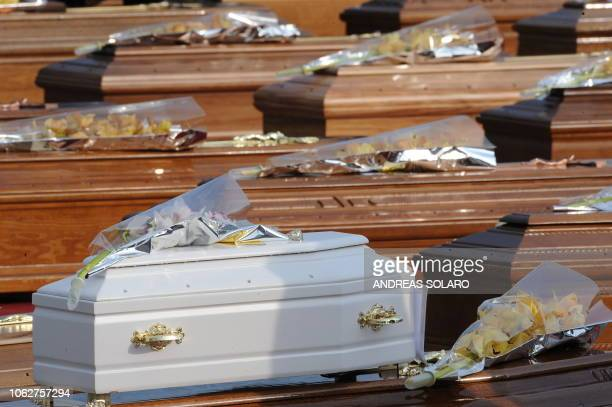 The coffin of a child is laid on an adult one in the vast square courtyard of a Guardia di Finanzia police training centre where some 200 coffins...