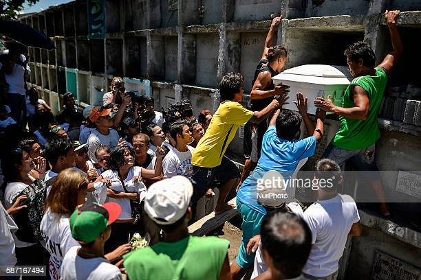 The coffin of a suspected drug pusher and victim of a vigilantestyle execution is placed on a tomb as relatives grieve during a burial ceremony in...
