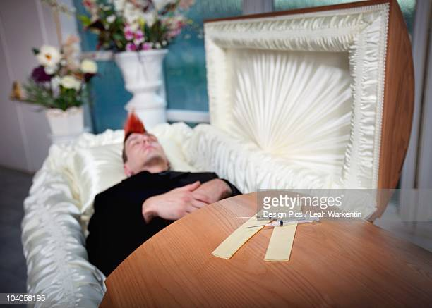 the coffin of a young man with syringes on top of it - drug overdose stock photos and pictures