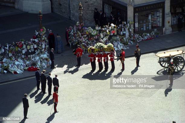 The coffin of Diana Princess of Wales is carried into Westminster Abbey by the Welsh Guardsmen watched by her sons Prince William and Harry her...