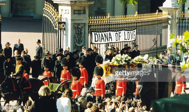 The coffin of Diana Princess of Wales passes a poster 'DIANA OF LOVE' as it leaves Buckingham Palace for her funeral at Westminster Abbey on...