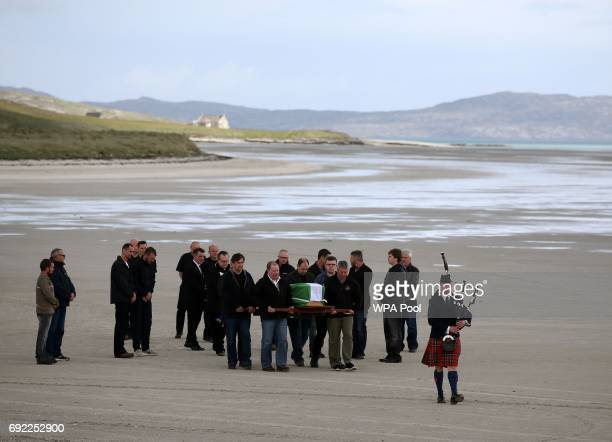 The coffin of Eilidh MacLeod draped in the Barra flag is carried across Traigh Mhor beach at Barra airport after it arrived by chartered plane on...
