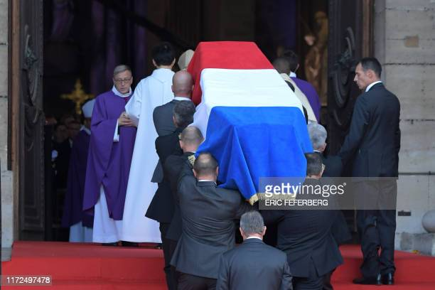 TOPSHOT The coffin of former French President Jacques Chirac covered with the French national flag is carried by pall bearers into the SaintSulpice...