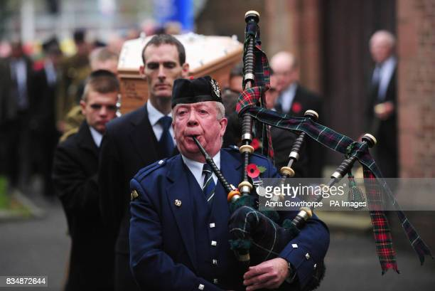 The coffin of Joseph Lappin is led away by a piper after his funeral service at St Oswald's Church Old Swan Liverpool