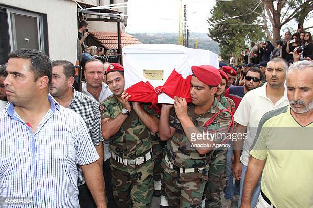 The coffin of Lebanese soldier Mohamed Assem Dahir who was killed by a roadside bomb near the border town of Arsal is carried by Lebanes soldiers...