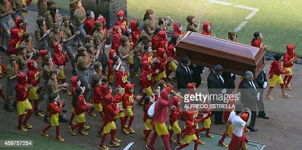 The coffin of Mexican comedian Roberto Gomez Bolanos is carried followed by children disguised as his characters El Chapulin Colorado and El Chavo...