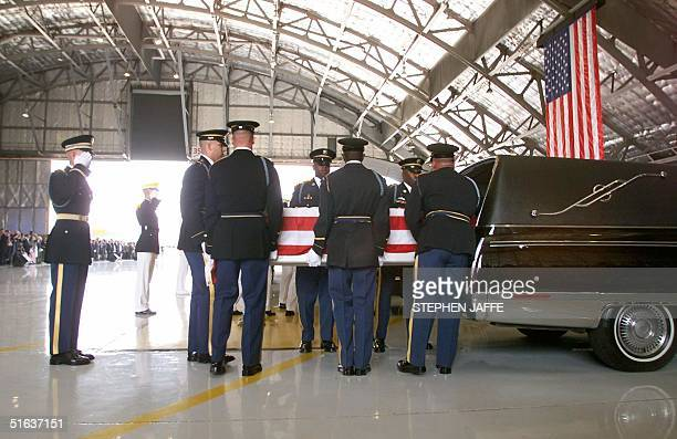 The coffin of one of the victims of the US Embassy bombings in Nairobi is loaded into a waiting hearse 13 August at Andrews Air Force Base MD Ten of...