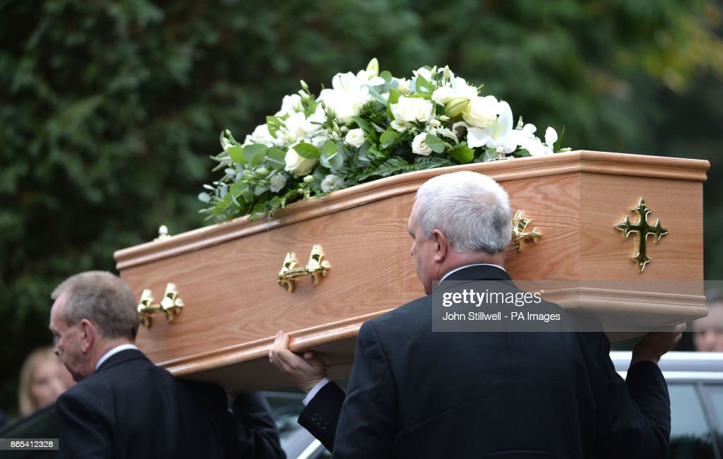 The coffin of Sean Hughes is carried into Islington and Camden Cemetery in London.