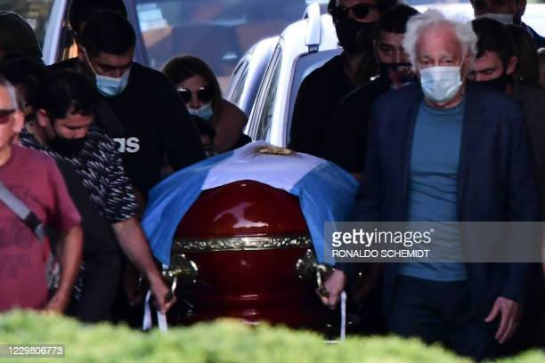 The coffin with the remains of late Argentine football legend Diego Armando Maradona is carried by his family and friends at the Jardin Bella Vista...