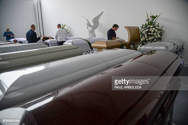 The coffins of the victims of a plane crash in the Colombian mountains are seen at the San Vicente mortuary in Medellin on December 1 2016 The pilot...