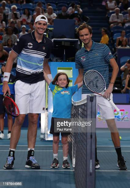 The coin tosser poses with John Isner of Team USA and Daniil Medvedev of Team Russia during day three of the 2020 ATP Cup Group Stage at RAC Arena on...