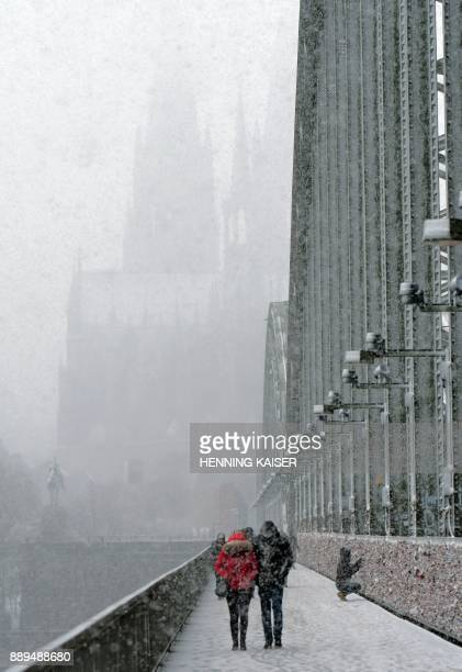 The Cologne Cathedral is almost univisible in the background as people walk over the Hohenzollern Bridge during heavy snowfall in Cologne western...