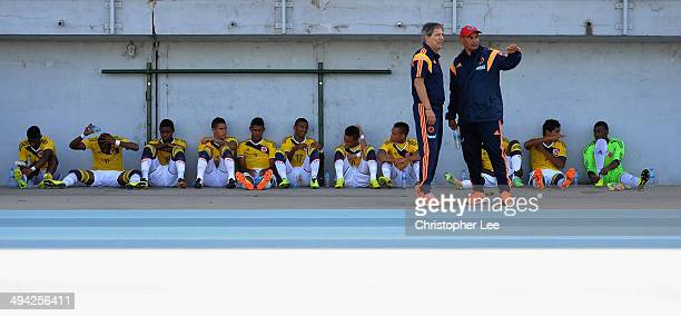 The Colombia team rest in the shade of the stand as their head coach Carlos Restrepo talks tactics with his assistant during the Toulon Tournament...