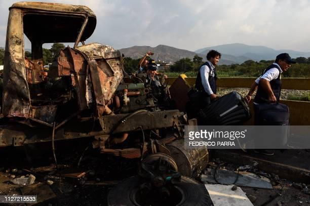 The Colombian Consul in Merida Venezuela Carlos Garcia walks next to a burnt truck as he crosses the Simon Bolivar international bridge from San...