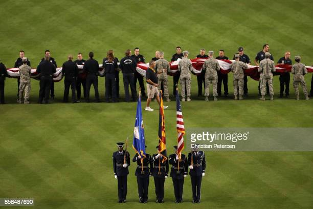 The color guard stand attended before the american flag is revealed during the National League Wild Card game between the Arizona Diamondbacks and...