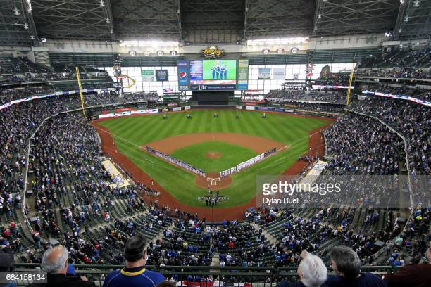 The Colorado Rockies and Milwaukee Brewers stand for the national anthem before the MLB opening day game at Miller Park on April 3 2017 in Milwaukee...