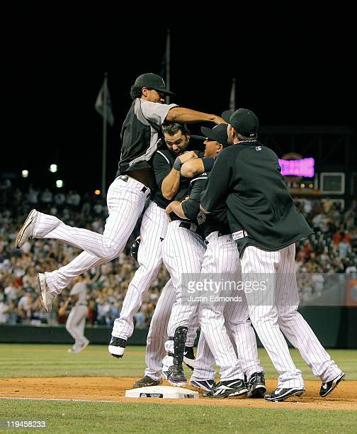 The Colorado Rockies pile on top of Carlos Gonzalez after he hit a walkoff RBI single in the bottom of the ninth inning as the Rockies defeated the...