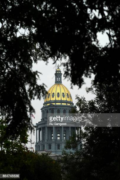 The Colorado State Capital building is seen through trees at Civic Center Park on September 27 2017 in Denver Colorado
