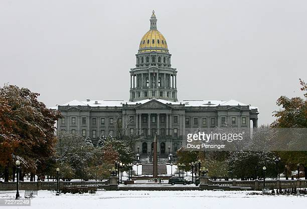 The Colorado State Capitol Building stands across a snow covered Civic Center Park after an early season snowstorm on October 26 2006 in Denver...