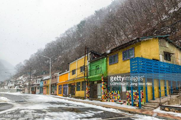 the colorful village in the mountain range on a snowing winter day - gangwon province stock pictures, royalty-free photos & images