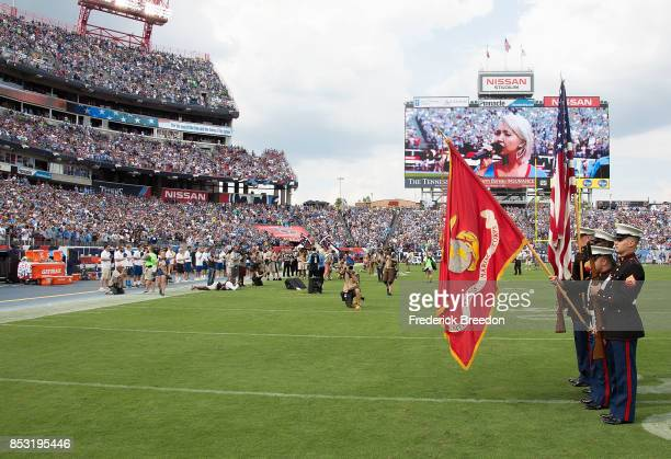 The colorguard presents the American Flag as the bench of the Tennessee Titans remains empty during the national anthem prior to a game between the...