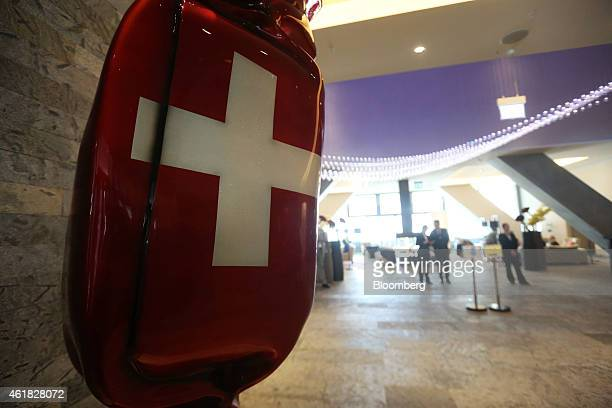 The colors of the Swiss national flag sit on a sculpture in the shape of a sweet hanging in the lobby of the InterContinental hotel operated by...