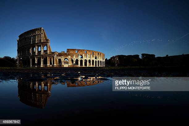 The Colosseum reflects in the water on November 21 2014 in Rome AFP PHOTO / FILIPPO MONTEFORTE