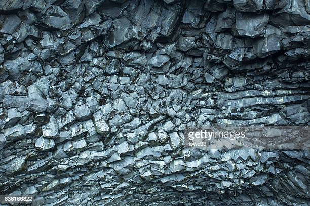 Adjacent to the world-famous Reynisfjara black sand beach in South Iceland, there is a mountain called Reynisfjall. At the base of the mounatain on the beach side, there is a cave that the roof consists of colums of basalt.