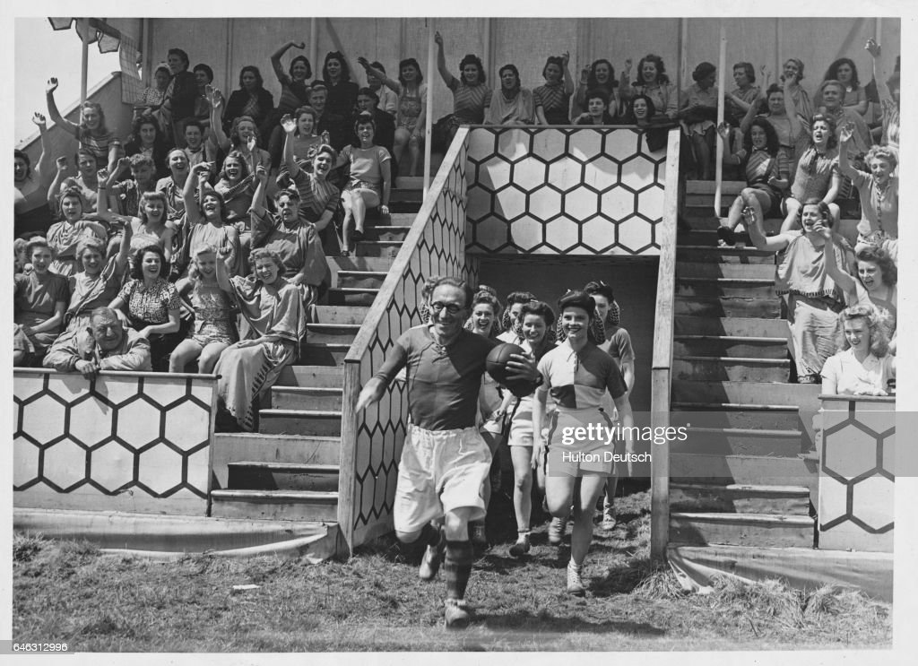 The comedian Arthur Askey leads out a team of female rugby players cheered on by a stand of supporters.