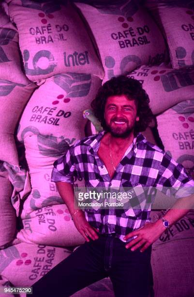 The comedian Beppe Grillo smiling in front of some coffee bags in the Tv show Te lo do io il Brasile 1984